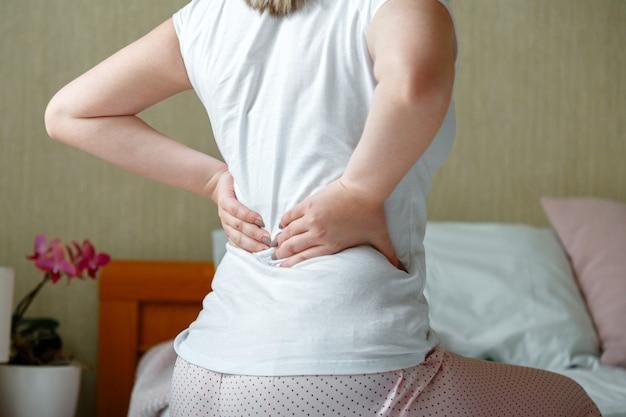 Rückenschmerzfrau, die nach dem aufwachen bekommt. kranke person mit rückenschmerzen in der wirbelsäule. nicht erkennbare frau im schlafzimmer hat nach dem schlafen lenden- und kreuzschmerzen.