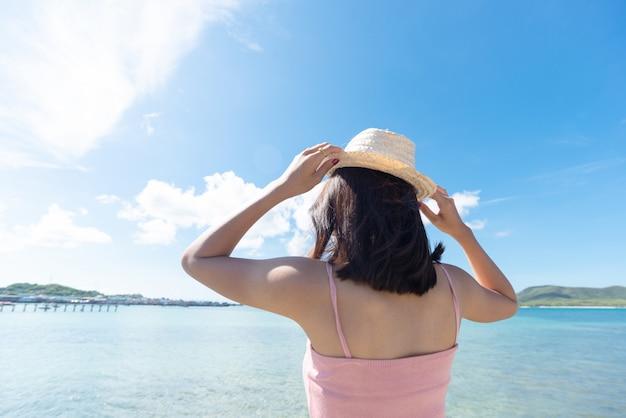 Rückseite der asiatischen frau tan haut tragen rosa trägershirt und halten strohhut. sie schaut ins meer. sommerreise. entspannen.