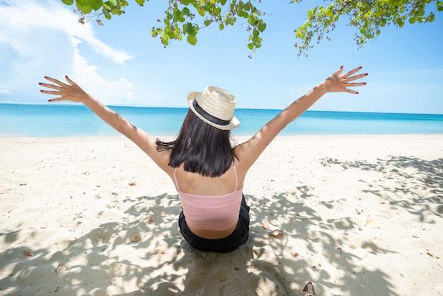 Rückseite der asiatischen frau tan haut tragen rosa trägershirt und strohhut sitzen am strand unter baum und stehende arme ausgestreckt am himmel. sommerreise. entspannen.