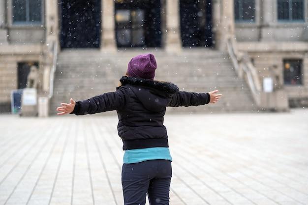 Rückseite der asiatischen jungen frau, die den schnee spielt, als schnee gerade fiel, reise und aufgeregtes konzept