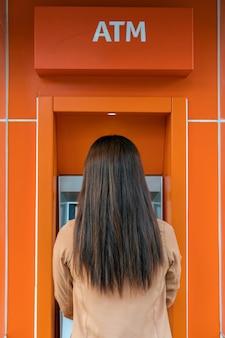 Rückseite der frau das bargeld über atm zurückziehend, geschäft automatic teller machine-konzept