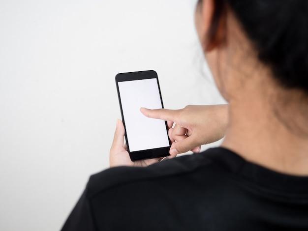 Rückseite der frau, die handy benutzt, um social media zu überprüfen und weißen bildschirm zu kaufen