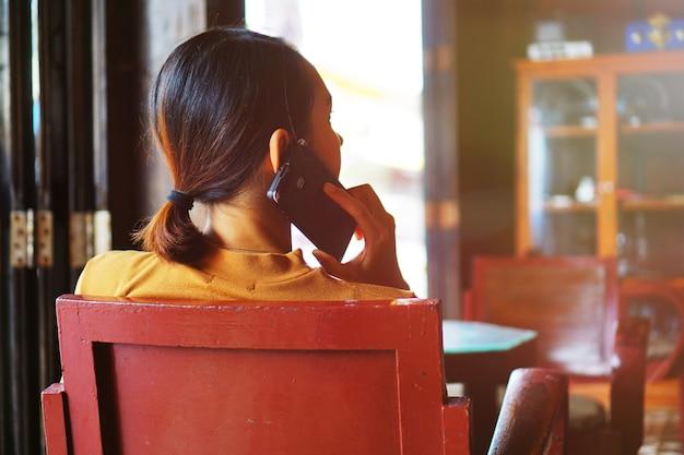 Rückseite der frau, die smartphone im café mit aufflackernlicht- und -unschärfehintergrund spricht
