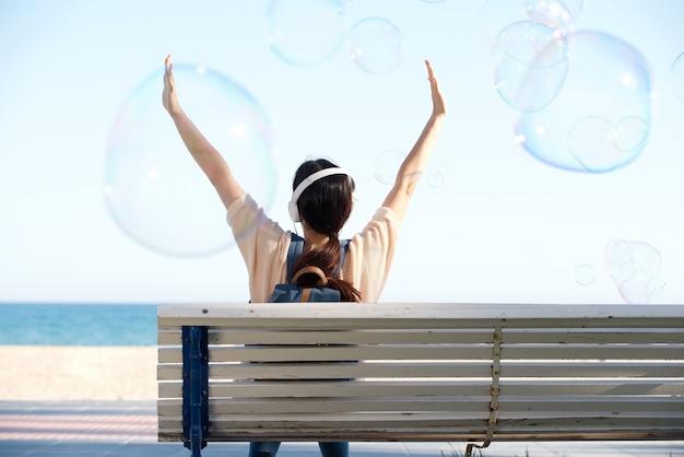 Rückseite der frau mit den armen ausgestreckt durch meer mit luftblasen