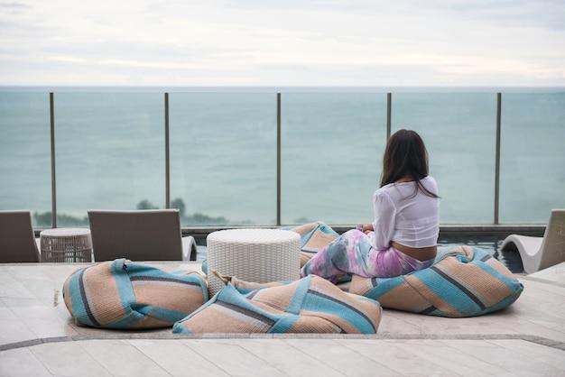 Rückseite der jungen asiatischen frau auf weichem sitzsack, um sich zu entspannen und blick auf die küstenlandschaft auf das dach des hotelschwimmbades zu sehen. luxusreisen oder urlaub im sommer in hua hin.