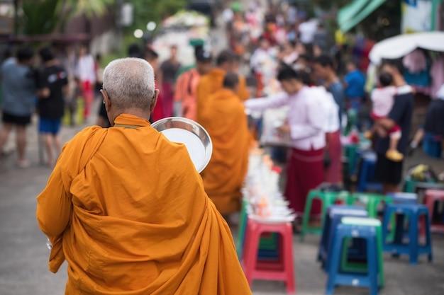 Rückseite des alten mönchs mit weißem haar, der von mon-leuten und vielen reisegästen im dorf sangkhla buri zu almosen geht?