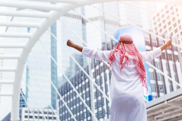 Rückseite des arabischen geschäftsmannes seine hände in der luft steigend