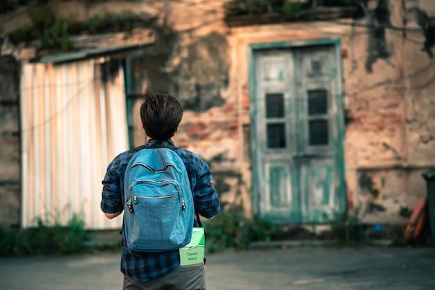 Rückseite des asiatischen reisenden im blauen karierten hemd mit dem rucksack, der in thailand reist