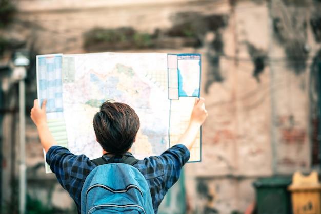 Rückseite des asiatischen reisenden im blauen karierten hemd suchen auf der karte nach dem reisen in alten schlepptau