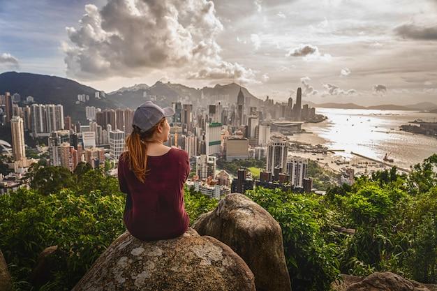 Rückseite des asien-frauenreisenden sitzend, nachdem die spitze von hong kong-berg geklettert worden ist und hong kong- und kowlloon-stadtbild wenn sonnenuntergangzeit, abenteuer geschaut worden ist