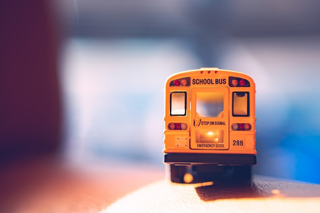 Rückseite des gelben miniaturschulbusses mit sonnenlicht - weinlesefilter