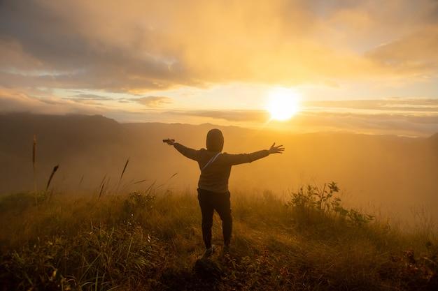 Rückseite des glücklichen frauenstandplatzes auf dem spitzenberg, der ansicht mit sonnenaufgang und nebel doi langka luang, chiang rai-provinz betrachtet. weicher fokus.
