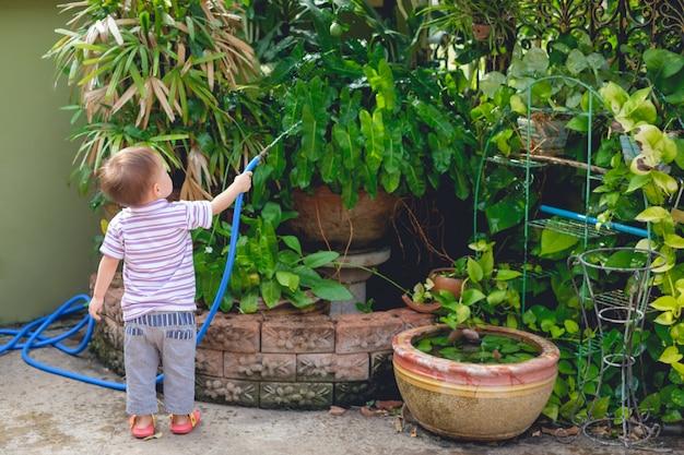 Rückseite des kleinen asiatischen 2 jahre alten kleinkindbabys, das spaß hat, die pflanzen vom schlauchspray im garten zu hause zu gießen, kleiner heimhelfer, hausarbeit für kinder, kinderentwicklungskonzept