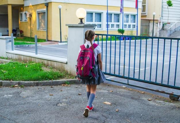 Rückseite des mädchenkindes, das zur schule mit purpurrotem rucksack geht. wandern zum schuletor