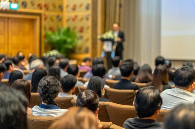 Rückseite des publikums, das den sprecher mit podium auf der bühne in der konferenzhal hört