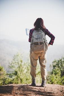 Rückseite des reisenden mädchen sucht richtige richtung auf karte, während der reise zum wandern in den bergen. reisekonzept