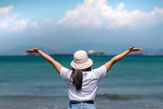 Rückseite des schönen mädchens verlängern arme und glücklich am strand inmitten des blauen himmels
