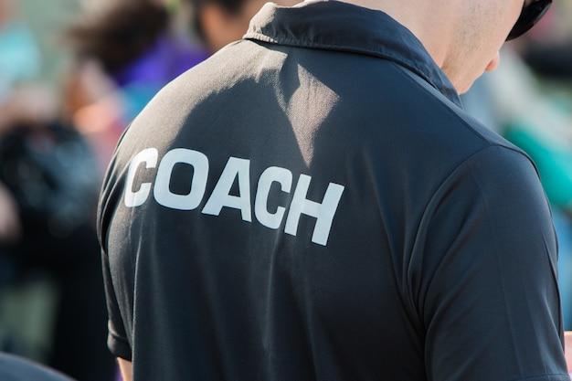 Rückseite des schwarzen farbenhemdes eines trainers mit dem wort trainer, der an geschrieben wird