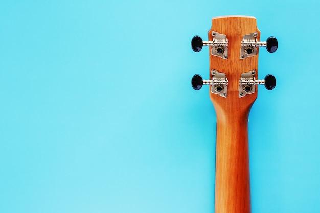 Rückseite des ukulelehalses auf blauem hintergrund