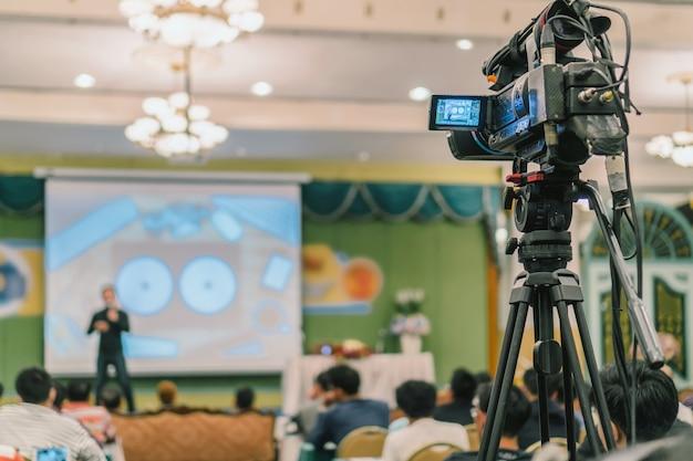 Rückseite des video-kameramanns, der foto zum asiatischen sprecher mit beiläufigem anzug auf dem st. macht
