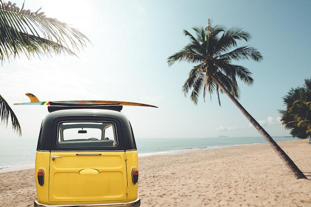 Rückseite des weinleseautos parkte auf dem tropischen strand mit einem surfbrett