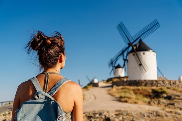 Rückseite einer frau in sommerkleidung und einer tasche mit blick auf alte windmühlen in consuegra, spanien.