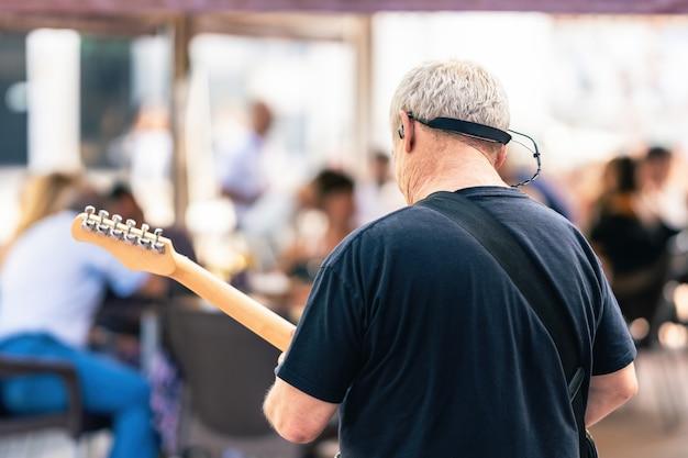 Rückseite eines älteren mannes, der bei einem live-konzert auf der terrasse e-gitarre spielt