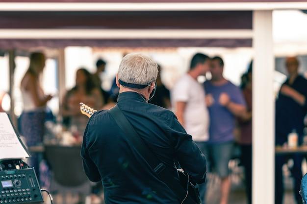Rückseite eines alten mannes, der auf einer terrasse mit publikum e-gitarre spielt