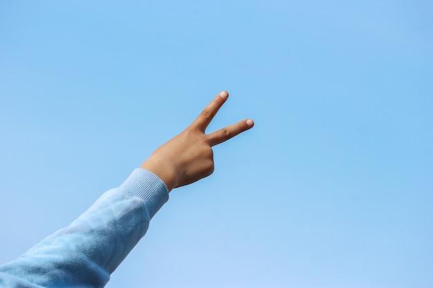 Rückseite eines siegeszeichens von einer hand des jungen mädchens mit blauem himmel als hintergrund.
