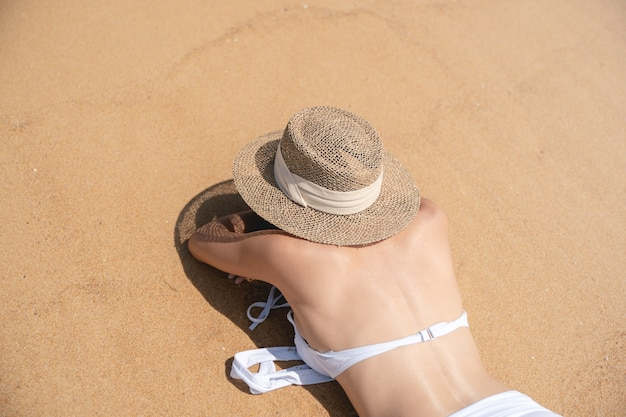 Rückseite frau im bikini liegend am sandstrand entspannendes sonnenbaden.