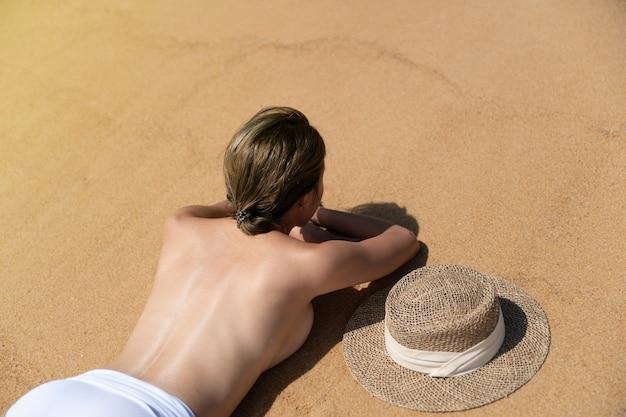 Rückseite frau oben ohne liegend am sandstrand entspannendes sonnenbaden.