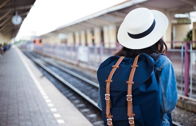 Rückseite von asiatischen frauentouristen, die eine tasche von schwarzen gläsern tragen, einen hut tragen und eine karte am bahnhof halten.