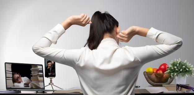 Rückseitenansicht der universitätsstudentenfrau fühlen sich schlafend, müde von videokonferenz-online-freunden auf dem geräteheft