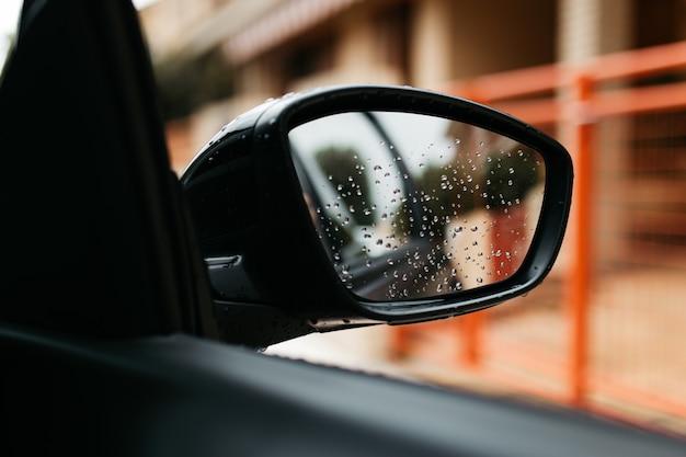 Rückspiegel durch das glas gesehen. nasses autofenster. regen tropfen hautnah. autoansicht sehen den spiegel.