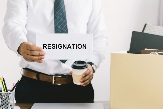 Rücktrittsgeschäftsmann, der persönliche firmengüter in einem braunen karton verpackt