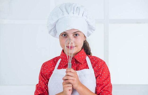 Rührbesen zum kochen verwenden. kochschule. traditionelle küche. kind hat spaß in der küche. kind und backen. gesundes essen und lifestyle-konzept. mädchen, das teig mit schläger macht. diät und gesundheit.