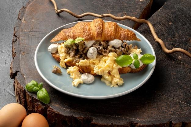 Rührei-croissant mit trüffel-dressing und pilzen.