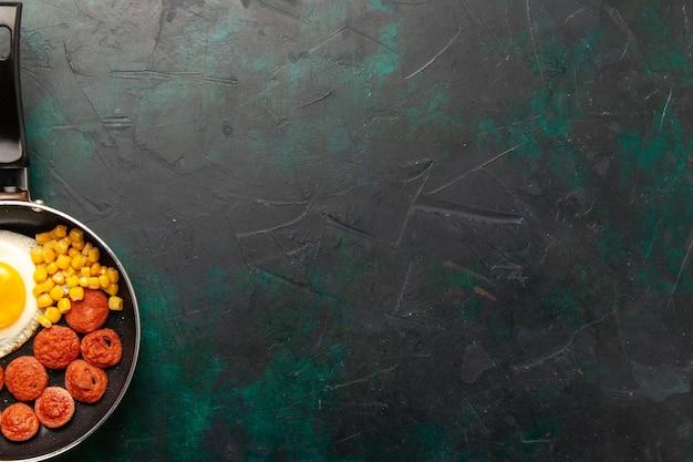Rührei der draufsicht mit geschnittenen würstchen und grüns innerhalb der pfanne auf dem dunklen hintergrund