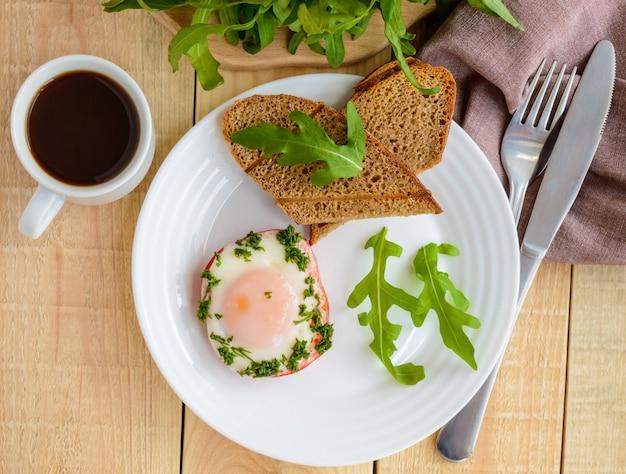 Rührei, gebacken in einem ring paprika, toast, rucola-blätter und eine tasse kaffee. leichtes frühstück. die draufsicht