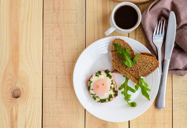 Rührei, gebacken in einem ring paprika, toast, rucola-blätter und eine tasse kaffee. linker platz für text. leichtes frühstück. die draufsicht
