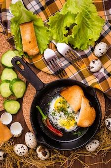Rührei in einer eisenpfanne, pfeffer, gurke und gebratenem brot. draufsicht