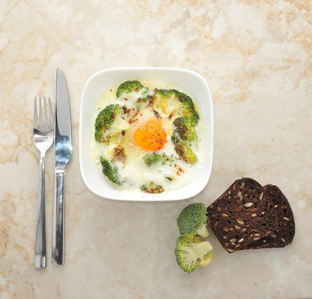Rührei mit brokkoli, brot mit sonnenblumenkernen und einem messer mit einer gabel