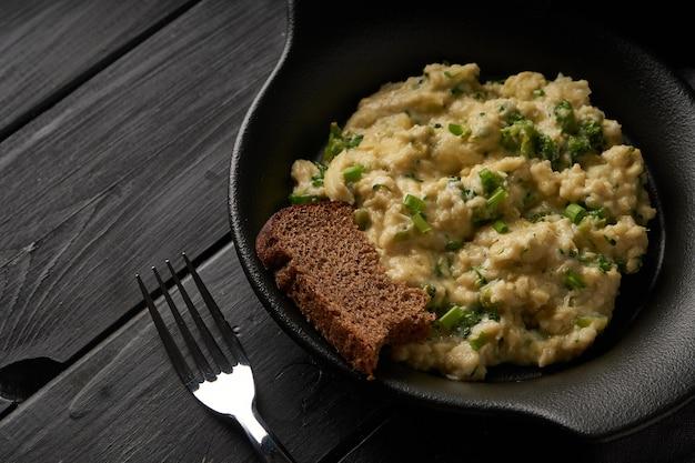 Rührei mit brokkoli und frühlingszwiebeln serviert in dunkler platte mit brot auf schwarzem tisch