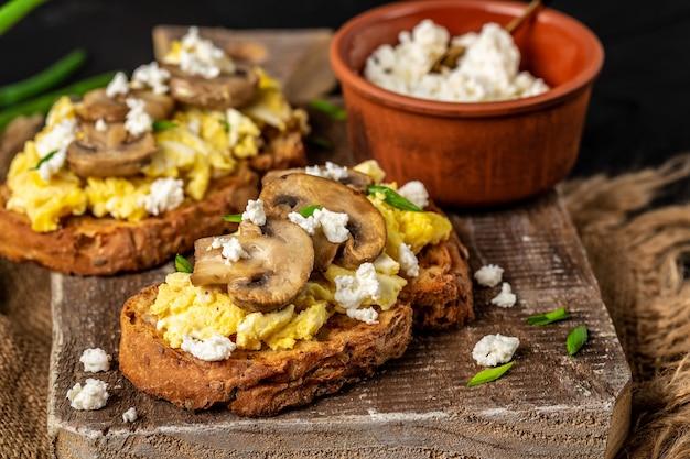 Rührei mit champignonpilzen auf knusprigem weizen-roggen-brot, gesundem frühstück oder brunch.