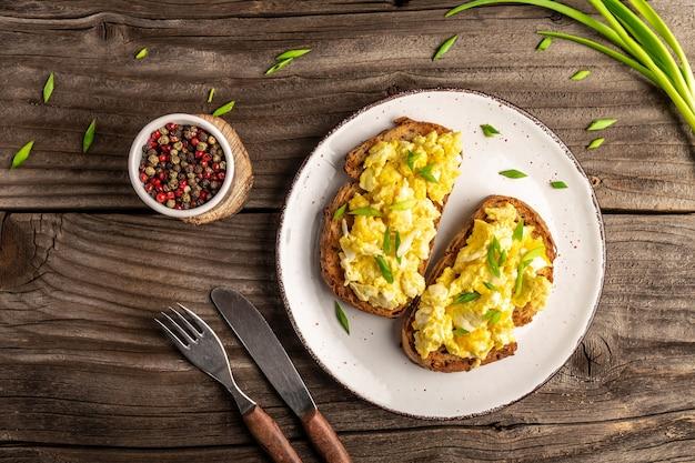 Rührei mit frühlingszwiebeln auf knusprigem weizenroggen-vollkornbrot, hausgemachtem, gesundem frühstück oder brunch.