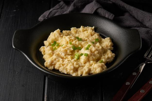 Rührei mit frühlingszwiebeln serviert in dunkler platte mit brot auf dem tisch