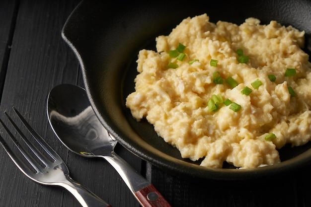 Rührei mit frühlingszwiebeln serviert in dunkler platte mit brot auf schwarzem tisch