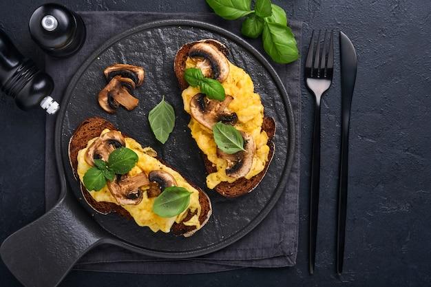 Rührei mit gebratenen pilzen und basilikum auf brot auf schwarzem tischhintergrund. hausgemachtes frühstück oder brunch - sandwiches mit rührei und pilzen. draufsicht mit kopienraum