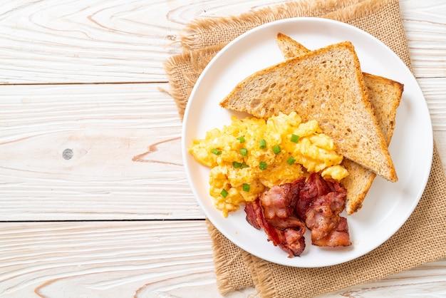 Rührei mit geröstetem brot und speck zum frühstück
