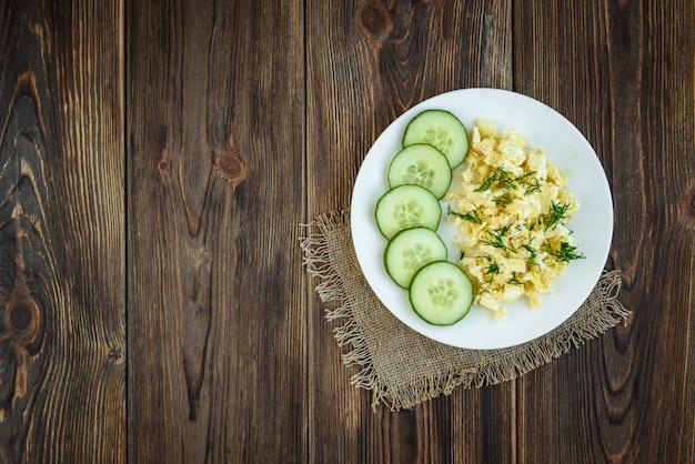 Rührei mit käse und gurke auf hölzernem hintergrund.